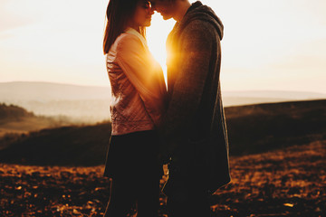 Side view of crop young man and woman touching noses while standing on background of amazing countryside and beautiful sundown sky.Crop couple against sunset sky Wall mural