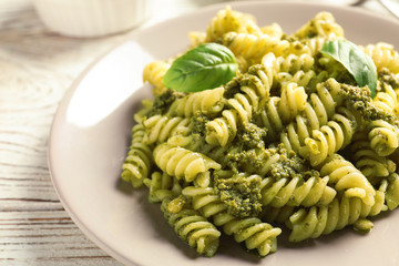 Plate with delicious basil pesto pasta on table
