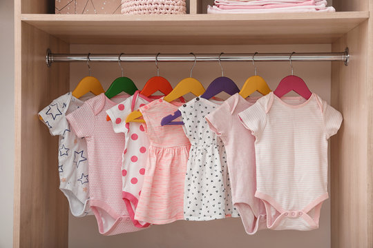Hangers with baby clothes on rack in wardrobe