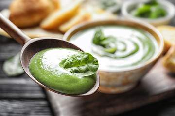 Spoon with fresh vegetable detox soup made of spinach on blurred background, closeup