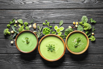 Flat lay composition with different fresh vegetable detox soups made of green peas, broccoli and spinach in dishes on table. Space for text