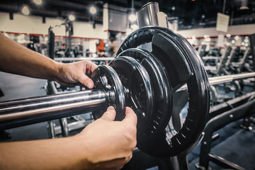 Close up of man's hands adjusting weight plates on barbell in gym