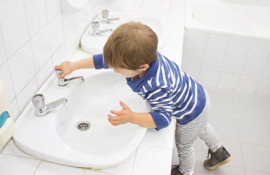 3 years boy washing hands at adapted school sink
