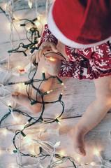 Baby boy playing with Christmas lights