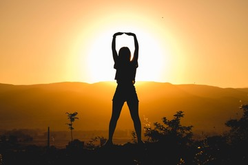 Silhouette of woman exercising during sunset