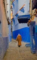 Man with a traditional dress is walking in the blue medina of Chefchaouen, Morocco