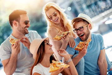 Close-up of four young cheerful people eating pizza