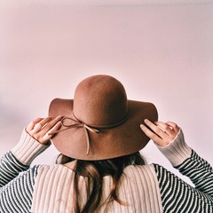 Close up of girl wearing hat against white background
