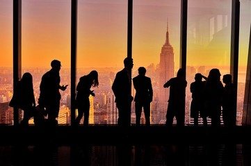 Silhouette of people standing against New York skyline at sunset