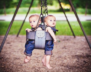 Boys swing together in park