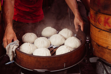 Young man cooking Chinese traditional steamed buns at the food stall