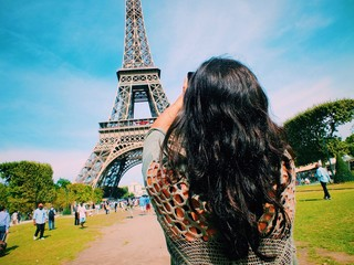 Rear view of woman taking picture of Eiffel Tower