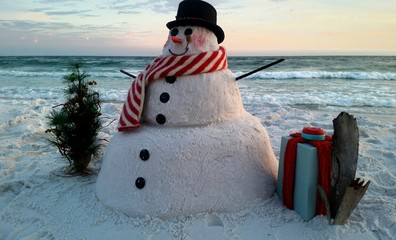 Snowman on snowy landscape against beach