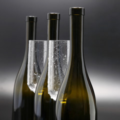 Three wine bottles and two empty wine glasses