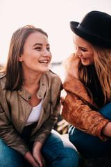 Smiling teenage girls sitting outdoors