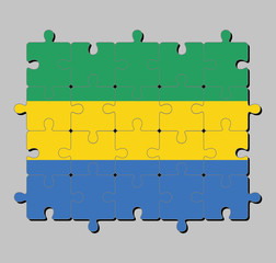 Jigsaw puzzle of Gabon flag in a horizontal triband of green, gold and blue. Concept of Fulfillment or perfection.
