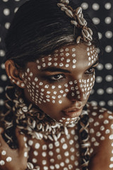 beautiful young attractive fashionable model portrait with traditional ornament  on skin and face