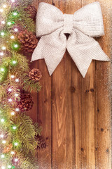 Big shiny bow and Christmas tree branches on natural wooden plank in background. Directly above.