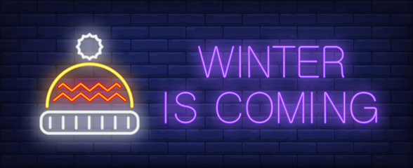 Winter is coming neon text with knitted hat. Christmas advertisement design. Night bright neon sign, colorful billboard, light banner. Vector illustration in neon style.