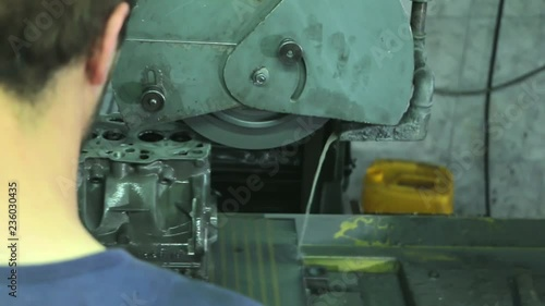 Worker grinding cylinder head and block on the machine  Cylinder
