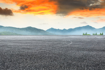 Asphalt road pavement and mountain at beautiful sunset Wall mural