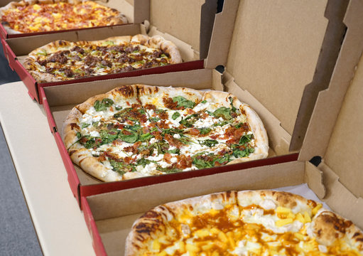 various pizza in boxes in a row for lunch