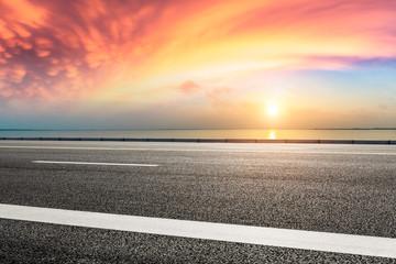 Asphalt road and dramatic sky with coastline at sunset Fototapete