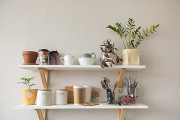 Fototapeta Nice shelves with various tableware and ceramic pots hanging on white wall in stylish room obraz