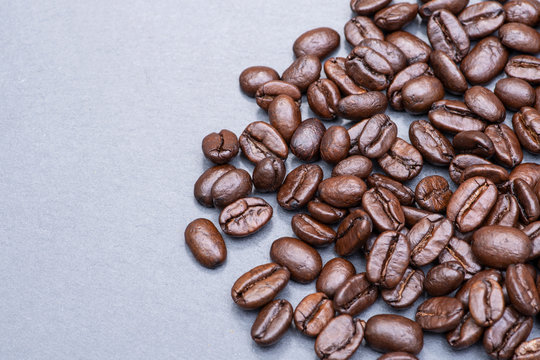 Macro shot of whole bean organic smooth medium dark roast coffee from Sumatra on natural stone background
