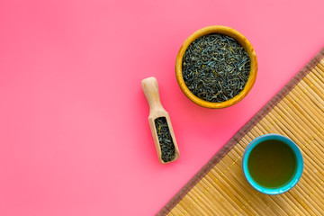 Chinese tea concept. Tea ceremony. Dry tea leaves in bowl and wooden scoop near cup of tea on pink background and bamboo table mat top view copy space