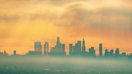 Fototapete - Downtown Los Angeles illuminated by epic rays of morning sunrise sun shining through clouds, zoom in on city skyline. 4K UHD Timelapse.