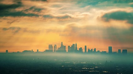 Fototapete - Downtown Los Angeles skyline illuminated by epic rays of morning sunrise sun shining on city through clouds. 4K UHD Timelapse.