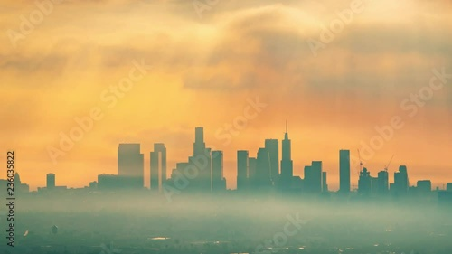Fotobehang Downtown Los Angeles illuminated by epic rays of morning sunrise sun shining through clouds, zoom in on city skyline. 4K UHD Timelapse.