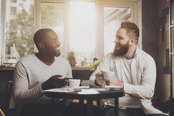 Multiethnic company of men communicates in a cafe