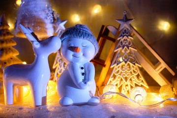 Funny Christmas snowman and reindeer in lights lamps in a winter scenery.  Christmas decoration - The magic of Christmas
