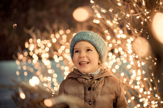 portrait of happy girl in winter evenings on background of Christmas lights