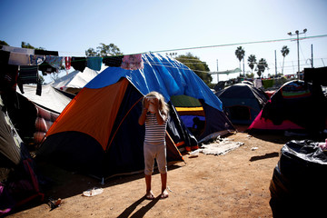 Cheili Mejia Meza, a migrant girl from Honduras, who is part of a caravan of thousands from Central America trying to reach the United States, wipes her face with wet tissue in front of her family's tent at a temporary shelter in Tijuana