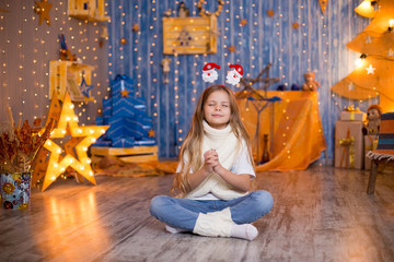 A girl dreams of gifts on a Christmas background of bright lights from the garland.