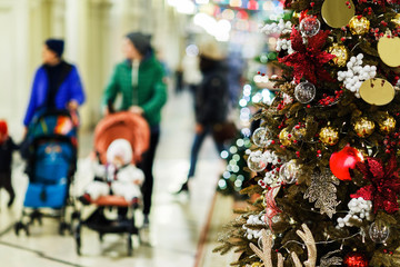 Photo of decorated spruce in store on background of moms with strollers