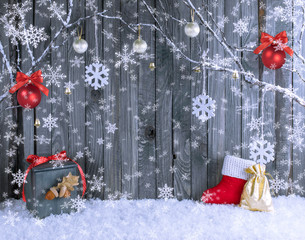 Christmas interior with decorative branches, Santa boot, gift bag and balls on wooden planks background