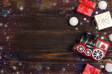 Winter holiday background with toy train, gift boxes and copy space on wooden table.