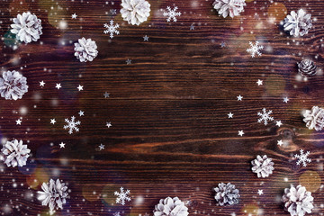 Winter holiday frame of snow painted pinecones, snowflakes and stars with copy space on wooden background.