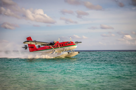 Seaplane landing in the ocean lagoon. The takeoff of a seaplane from the ocean beach.