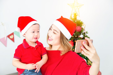 Beautiful asian mother with her son wearing christmas costume and taking photo themself by smartphone at home with christmas decoration