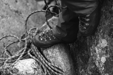 Legs of the climber in climbing boots against the backdrop of climbing rope. Black and white.
