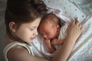 Sleeping children, sister embrace newborn baby