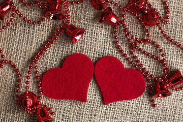 Two red hearts and red garland on rough background.