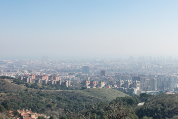 Overview of the polluted city of Barcelona, from the Collserola mountain, with a layer of smog over it.