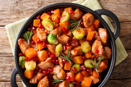 Delicious chicken cooked with vegetables and rosemary in pomegranate sauce close-up in a pan. horizontal top view