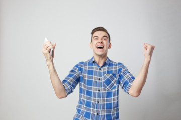 Ecstatic full of energy guy dressed in a plaid shirt keeps mobile phone in his hand a white background in the studio